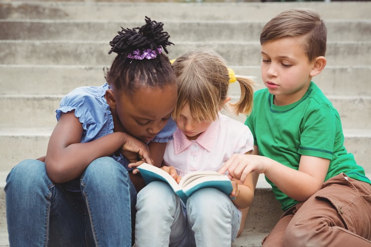 Students sitting on steps and reading a book