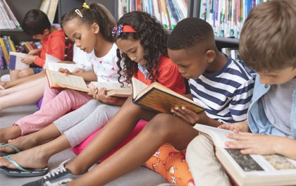 Children reading books in a school library.