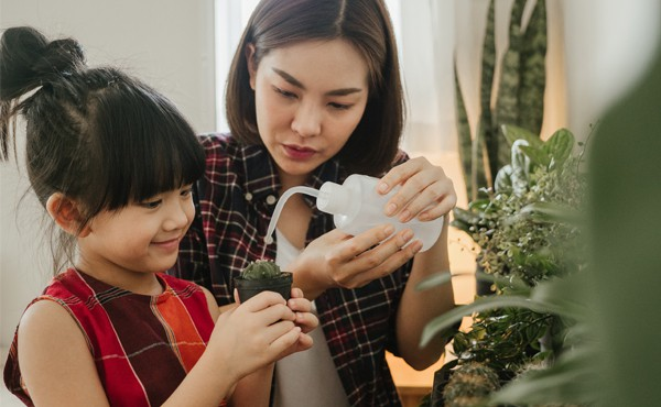 Mother and child watering plants indoors