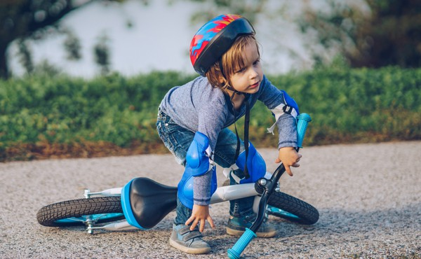 Boy picking himself up after fall from bicycle
