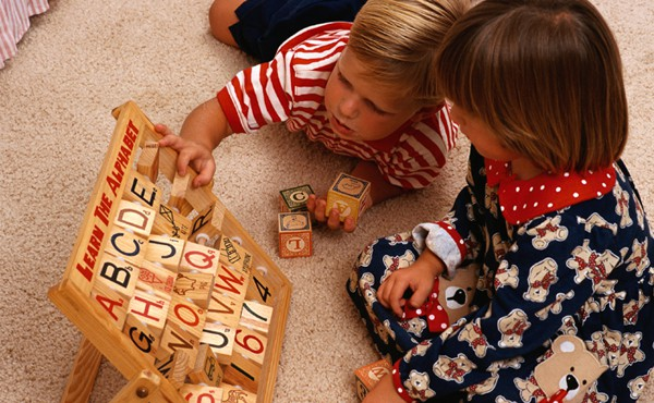 Young children playing with an alphabet block board