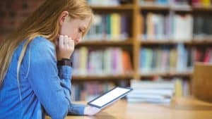 Student reading a tablet in school library