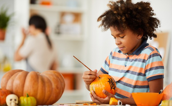 Child painting pumpkins for Halloween as their parent works on other crafts in background