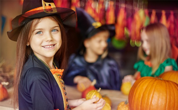 Girl in witch costume making crafts with pumpkins for Halloween