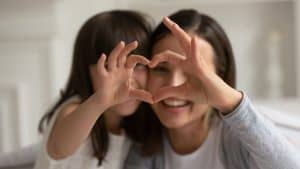 Mother and child making heart sign with hands. Gratitude can help children be happier and healthier
