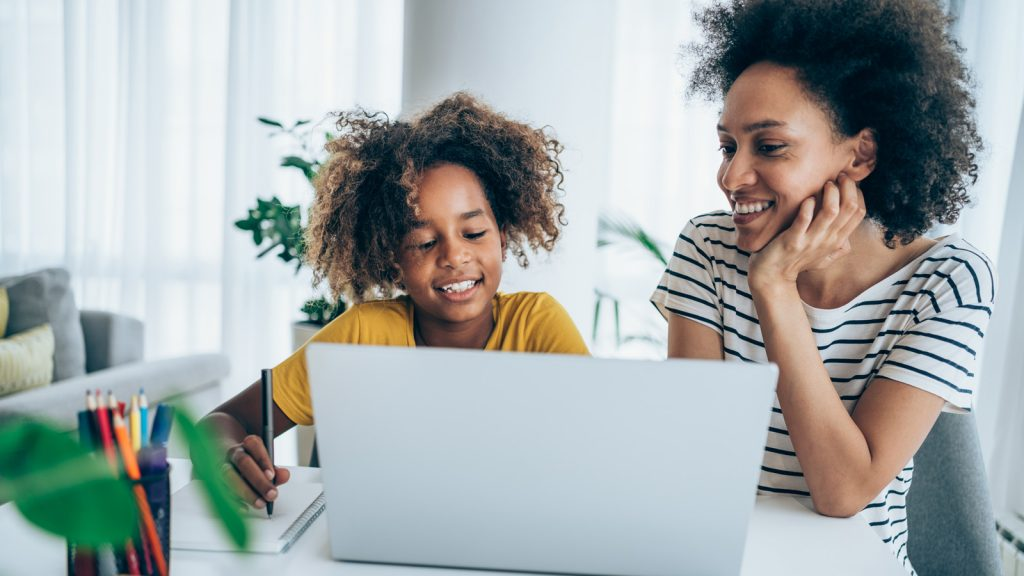 A mother and daughter looking up trivia answers on laptop