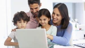 A family watching a young girl use the computer