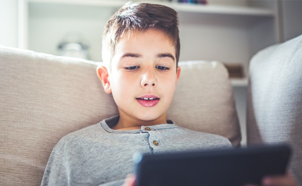 An elementary-age student reading the news on a tablet