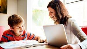 A boy and his caregiver use a laptop to do homework