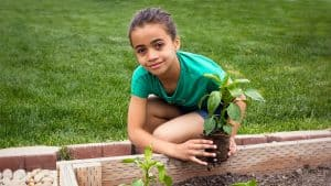 A girl in a backyard garden. Read how gardening with children helps them learn and grow