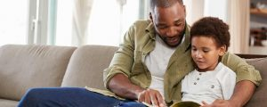 Father and son reading together. Spending quality time together is a good way to help your child cope with stress