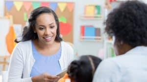 A speech therapist meeting with a teacher and child