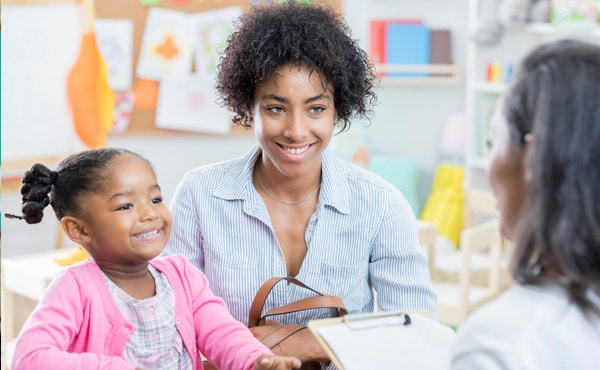 A family meets with their child's teacher. Using a two generation approach means educators can work to address the needs of a child's family at home, leading to success in school.