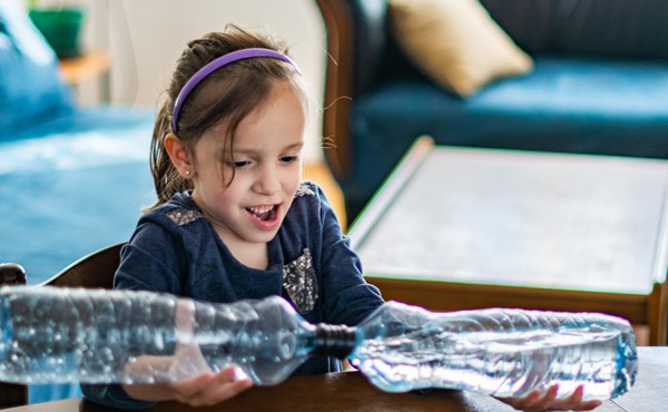 A girl makes a tornado in a bottle. Simple, reusable materials make for a fun science lesson