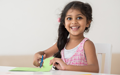 A young girl uses scissors to cut construction paper