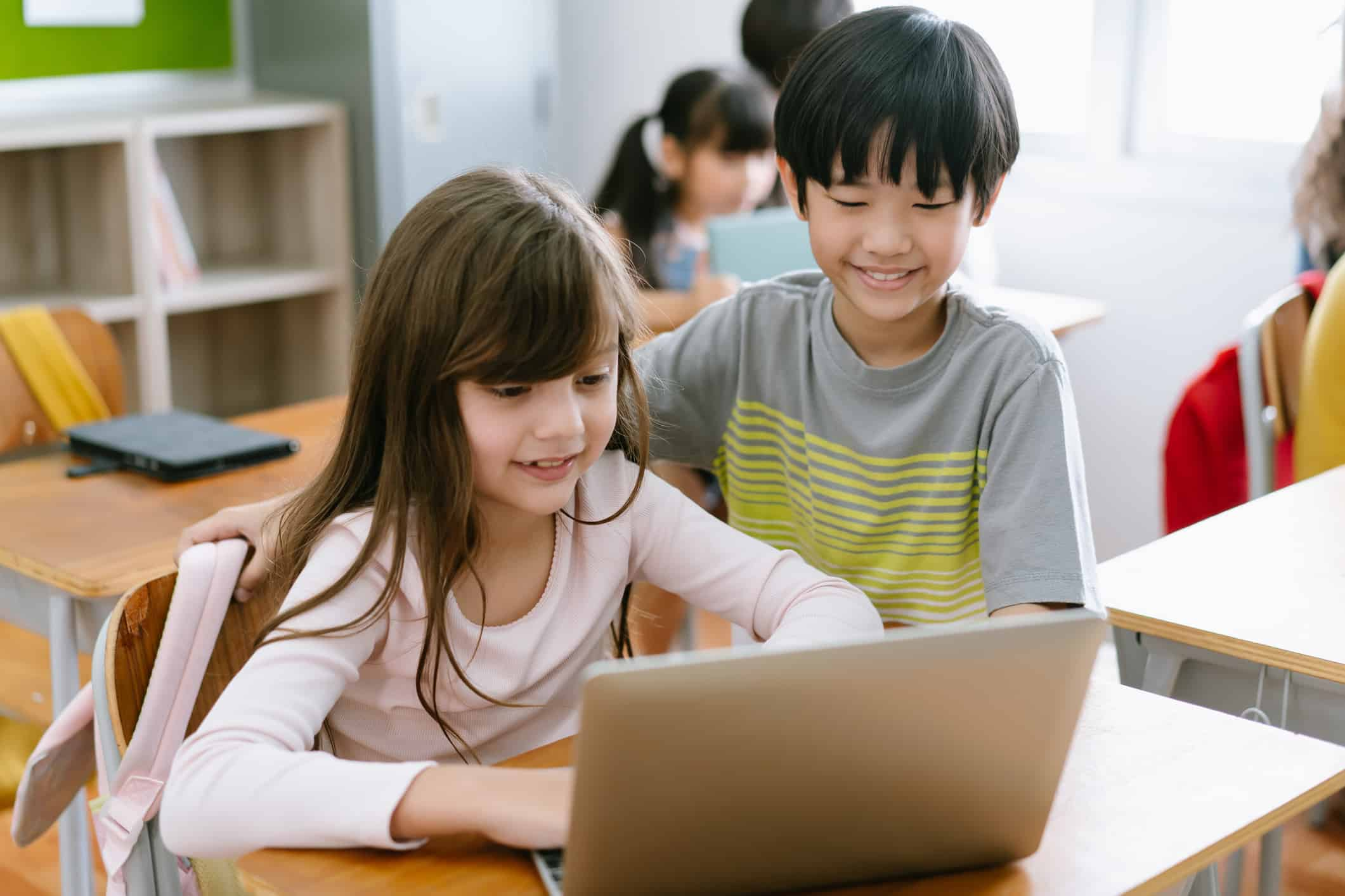Happy students in classroom using laptop or digital tablet in elementary school class. Education, elementary school, learning, technology and people concept.